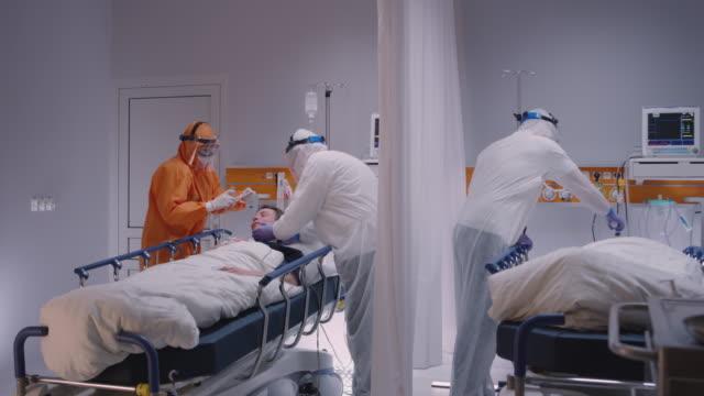 stockvideo's en b-roll-footage met arts in beschermend pak dat op zuurstofmasker op patiënt zet die aan coronavirus lijdt - brede langzame pop schot - gezondheidszorg beroep