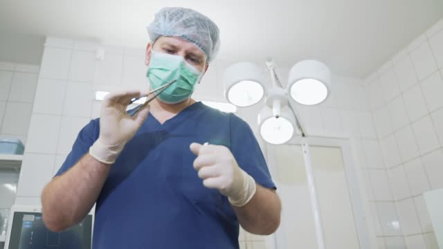 doctor in sterile white gloves and with a mask on his face examines medical instruments in the hospital. surgeon in the clinic dressed in professional clothes examines the clamp in the hands - lama oggetto creato dall'uomo video stock e b–roll