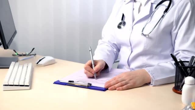 Doctor in uniform working in their office, filling out papers, writing a report