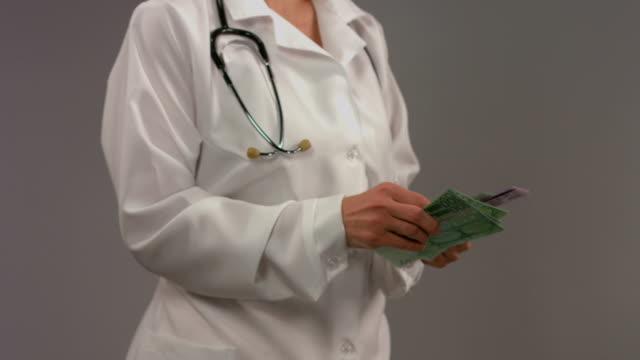 врач в белое пальто считать деньги.   поврежден системы здравоохранения - dollar bill стоковые видео и кадры b-roll