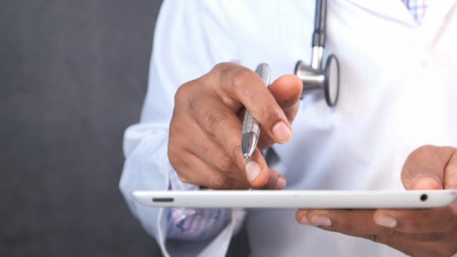 doctor in white coat is using a digital tablet doctor in white coat is using a digital tablet, general view stock videos & royalty-free footage