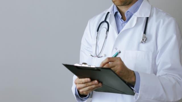 vidéos et rushes de docteur dans les documents d'écriture de manteau blanc sur le presse-papiers sur le fond gris - bloc note