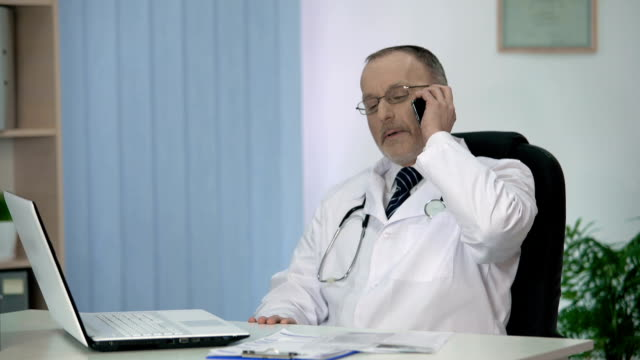 doctor inviting patient to hospital, talking about advantages of private clinic - oficjalne przyjęcie filmów i materiałów b-roll