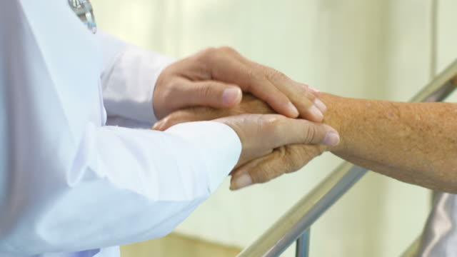Doctor is consoling patient by touching hand video