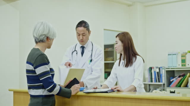doctor joining the conversation at hospital with patient and nurse - età miste video stock e b–roll