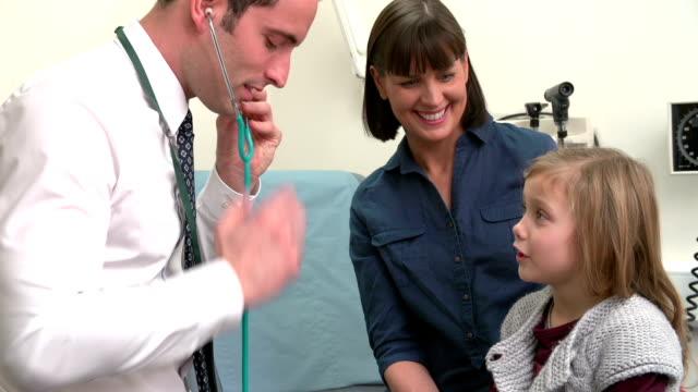 vídeos y material grabado en eventos de stock de médico escucha hijo en el pecho de la cirugía - pediatra
