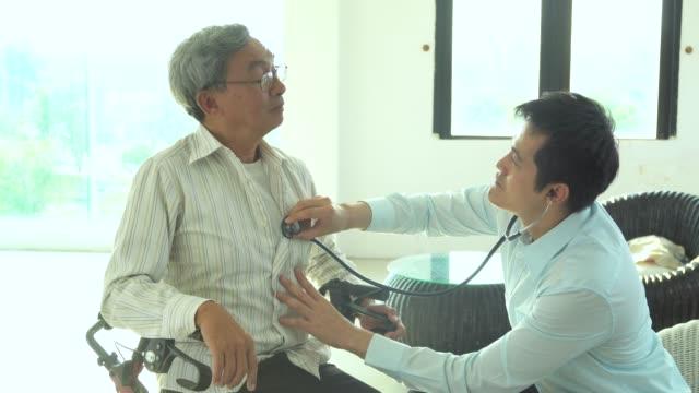 doctor listening to elder patient's heart - stetoscopio video stock e b–roll