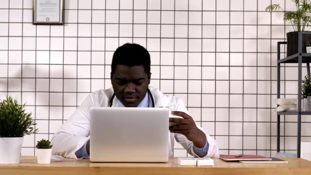 vídeos de stock e filmes b-roll de doctor looking at new tablets and checking info on laptop - jogos internacionais