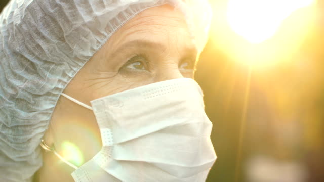 doctor looking forward at the sky - mask surgery video stock e b–roll