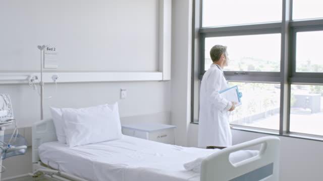 blick durch fenster am krankenhaus arzt - krankenstation stock-videos und b-roll-filmmaterial