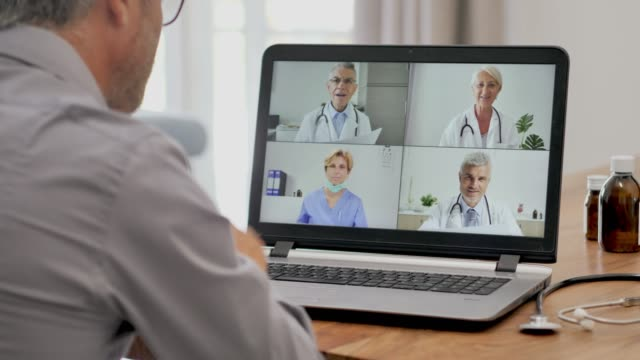 vídeos de stock e filmes b-roll de doctor makes video call conference with work colleagues - remote work