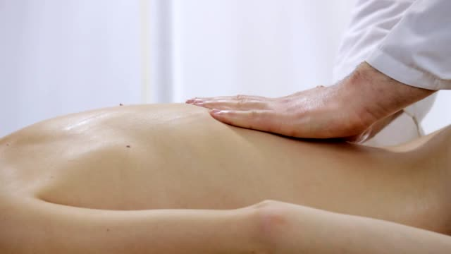 Doctor massage therapist relieves stress from a back a young girl, the camera pan video