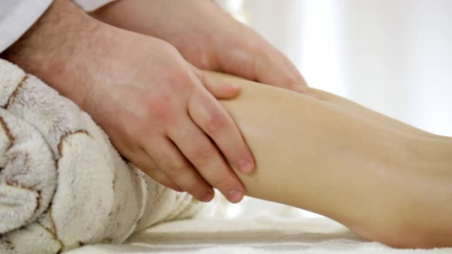 Doctor massage therapist relieves tension from gastrocnemius muscle of a young girl, the camera pan video
