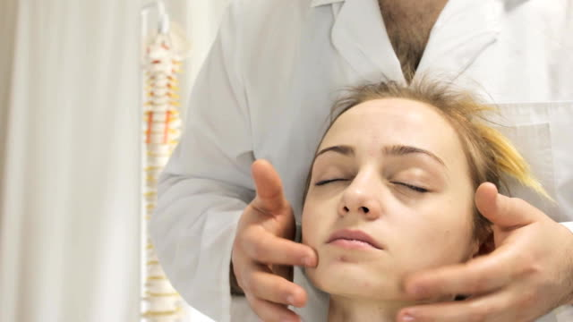 Doctor massages the face of a young girl with her fingers video