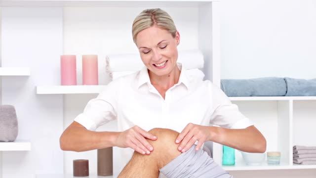 Doctor massaging her patients knee video