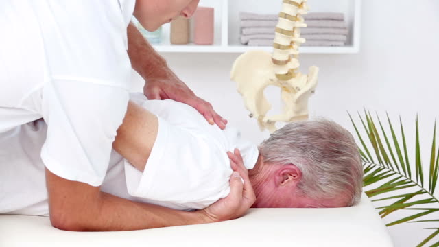 doctor massaging his patient shoulder - chiropractor stock videos and b-roll footage