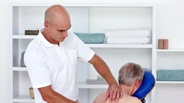 Doctor massaging his patients back video