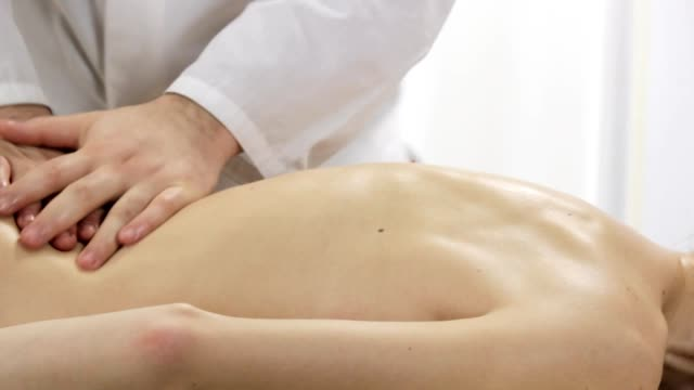 Doctor masseur doing back massage young girl video