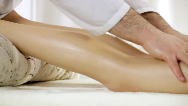 Doctor masseur doing leg massage for a young girl, removing tension from the calf muscles, the camera pan video
