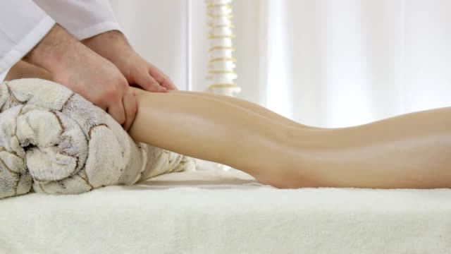 Doctor masseur doing massage of beautiful young girl legs video