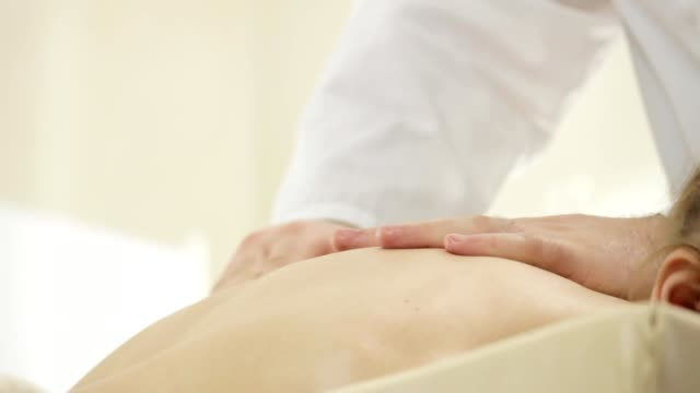 Doctor masseur doing shoulder massage, a young girl lying on a couch, the camera pan video