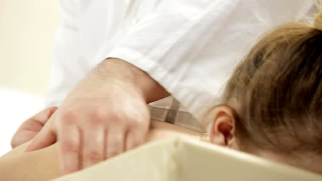 Doctor masseur doing shoulder massage for a young girl video