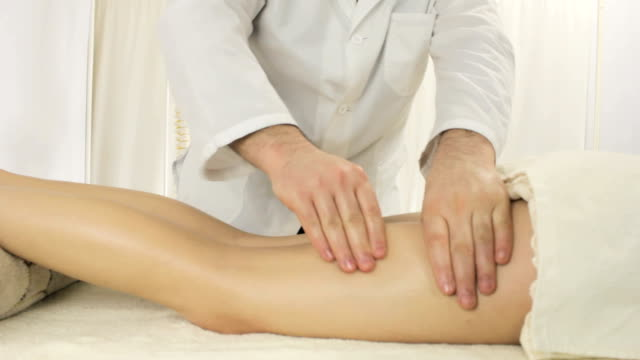 Doctor masseur lead a hands over entire length of legs, relax feet massage young woman in the salon video