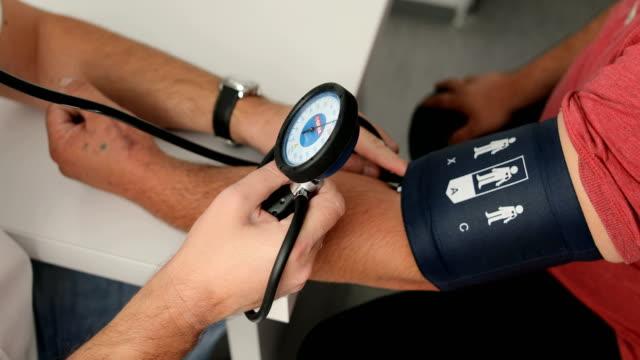 Doctor measuring blood pressure of male patient Doctor measuring blood pressure of male patient blood pressure gauge stock videos & royalty-free footage