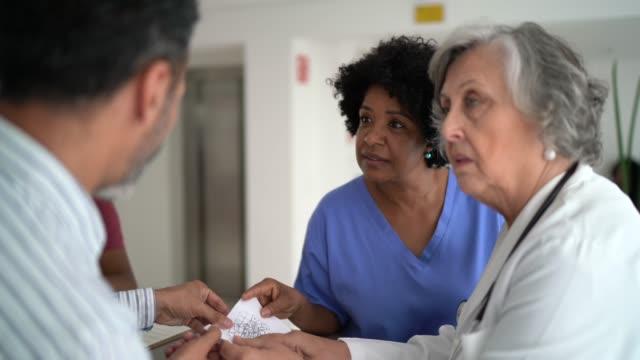doctor, nurse and patients at hospital secretary - ассистент стоковые видео и кадры b-roll