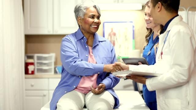 läkare, sjuk sköterska och senior vuxen patient på kontoret, klinik. - patient bildbanksvideor och videomaterial från bakom kulisserna