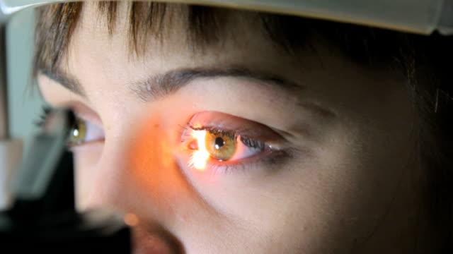 vidéos et rushes de opticien opthalmologue médecin examine le patient à l'aide de la rétine un instrument spécial, gros plan - examen ophtalmologique