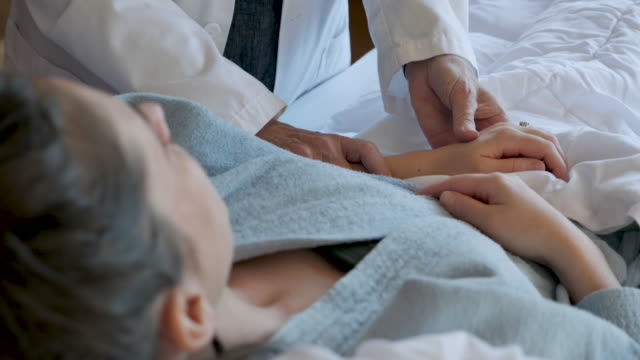 doctor or nurse patting the hand of a female patient lying in bed - sostegno emotivo video stock e b–roll