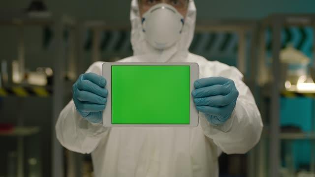 Arzt oder Forscher hält Tablet-PC mit grünem Bildschirm zur Kamera, stehend in modernen Labor. Konzept der Medizin, Technologie, Gesundheit und Menschen, Krankenhaus. Coronavirus , COVID-2019 oder H1N1 – Video