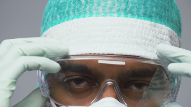 doctor or surgeon taking safety glasses off - occhiali protettivi video stock e b–roll