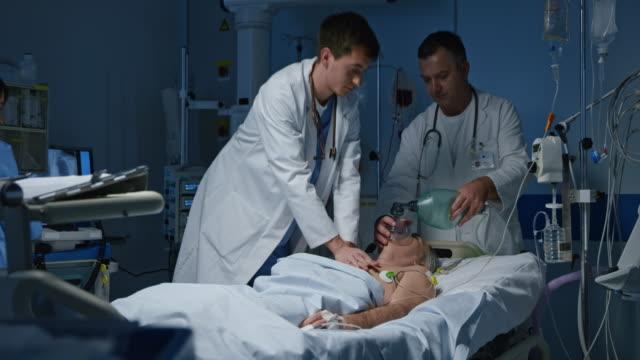 ds läkare utföra en hjärt-lungräddning på en patient i intensivvården - intensivvårdsavdelning bildbanksvideor och videomaterial från bakom kulisserna
