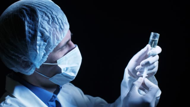 vídeos de stock, filmes e b-roll de médico pega uma vacina em uma seringa - braço humano