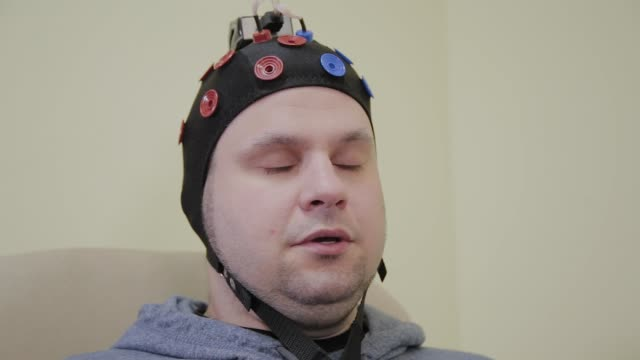 Doctor prepares headset for human brain research