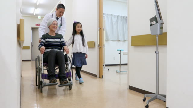 Doctor Pushes Senior Woman With Granddaughter Through a Hospital Doctor Pushes Senior Woman With Granddaughter Through a Hospital in a Wheelchair pushing wheelchair stock videos & royalty-free footage