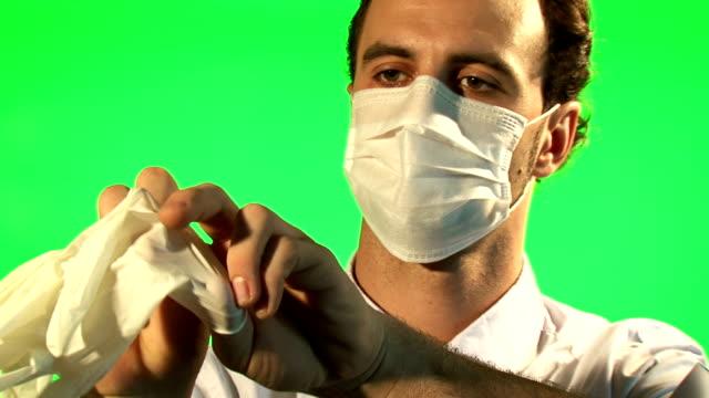 medico posiziona in maschera e i guanti chirurgici-verde schermo - guanto indumento sportivo protettivo video stock e b–roll