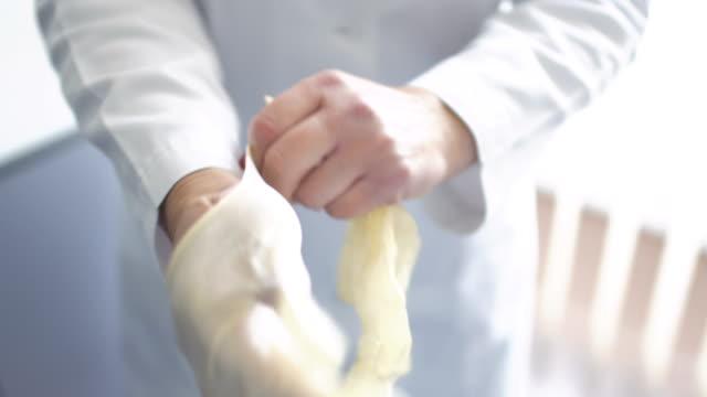 vídeos y material grabado en eventos de stock de doctor pone en guantes de goma - guante quirúrgico