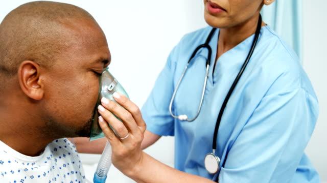 arzt den patienten eine sauerstoffmaske aufsetzen - sauerstoff stock-videos und b-roll-filmmaterial