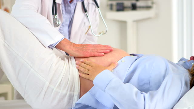 Doctor putting hands on pregnant woman's belly video
