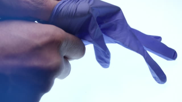 Doctor putting on a blue sterile blue latex glove Surgeon putting on a blue sterile glove ready for surgery. Filmed in 4K glove stock videos & royalty-free footage