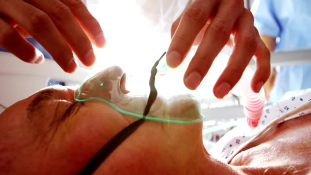 Doctor putting oxygen mask on a female senior patient face video