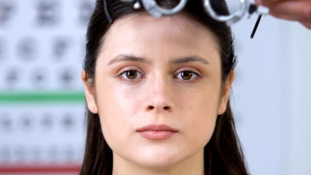 vidéos et rushes de docteur mettant le phoropter sur les yeux féminins de patient, essai ophtalmologique, vision - réfracteur