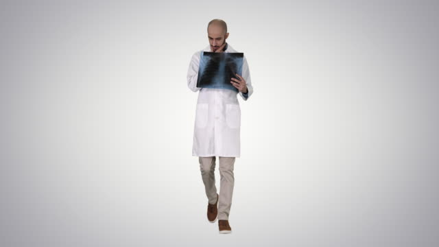 Doctor radiologist looking at x-ray scan walking on gradient background