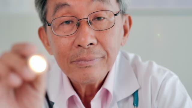 vidéos et rushes de docteur hommes aînés examinant l'oeil de patients avec le penlight dans hospital.medical, éducation, technologie, science, soins de santé, personnes et concept de médecine. consultation médicale.médecin et consultation des patients - rétine