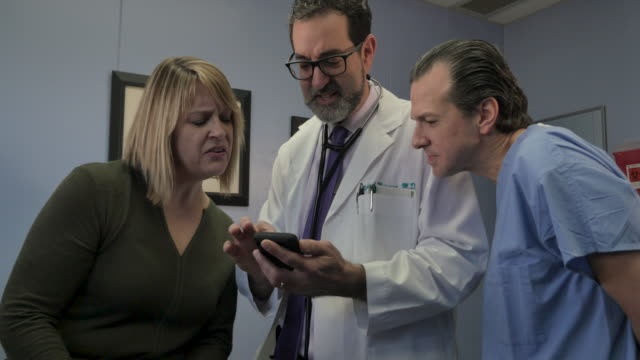 Doctor sharing information on a smartphone with a nurse and patient