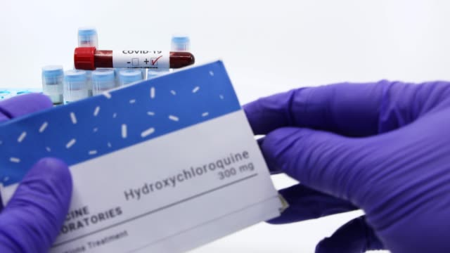 Doctor showing bottle of medicine for covid-19 treatment.Concept of Hydroxychloroquine medicine with blood tests tubes on the background.Cure for coronavirus,COVID-19 treatment. Dubai-UAE-Circa 2020:Doctor showing bottle of medicine for covid-19 treatment.Concept of Hydroxychloroquine medicine with blood tests tubes on the background.Cure for coronavirus,COVID-19 treatment. remdesivir stock videos & royalty-free footage