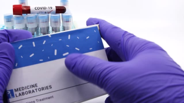 Doctor showing box of medicine for covid-19 treatment.Concept of Favipiravir medicine with blood tests tubes on the background.Cure for coronavirus,COVID-19 treatment. Dubai-UAE-Circa 2020:Doctor showing box of medicine for covid-19 treatment.Concept of Favipiravir medicine with blood tests tubes on the background.Cure for coronavirus,COVID-19 treatment. remdesivir stock videos & royalty-free footage